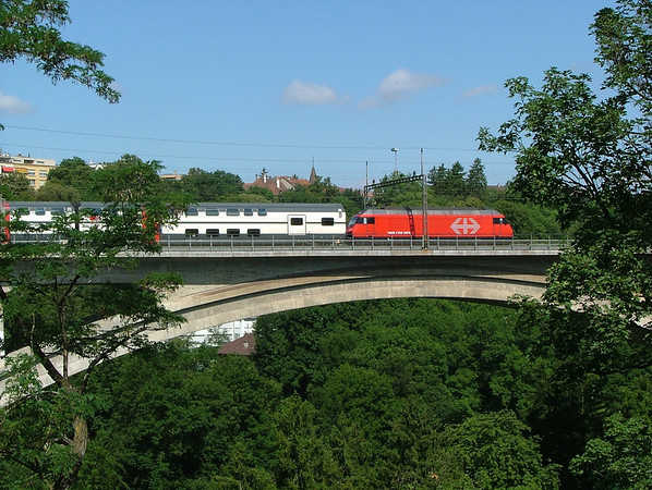 An Re460 with IC2000 double-deck stock crosses the Aare viaduct in Bern.